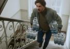 (Foto: SodaStream) Ein Vater wuchtet gequält 24 Flaschen durch das Treppenhaus.